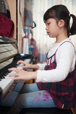 young girl playing piano in her home