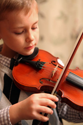 young boy playing the violin in his home
